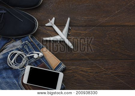 Table top view of object for traveler with technology concept background. Variety essential items on modern brown wooden office desk.Mix cloth for teenage or adult for travel with copy space.