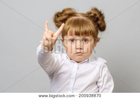 Portrait Of Little Girl Making Rock And Roll Sign