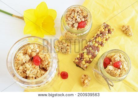 oat crunchy and crispy muesli bar with yellow narcissus flower, over table background, top view, healthy breakfast concept