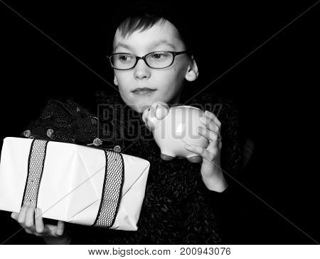 small boy or cute nerd kid in glasses hat and fashionable knitted scarf on black background holds white present box with red bow and pink piggy money box