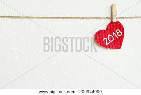Red fabric heart with 2018 word hanging on the clothesline over white wall background new year template