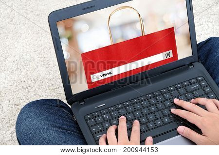 Hands using laptop computer with www. on search bar over blur store on screen background online shopping concept business and technology template