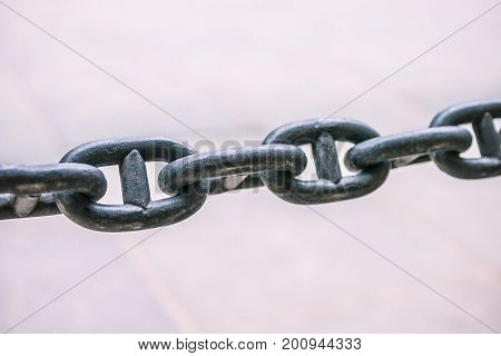 Close up of a rusty anchor chain on bright background.