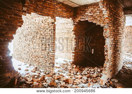 Destroyed and abandoned ruined building a few storey house broken windows and a broken brick facade