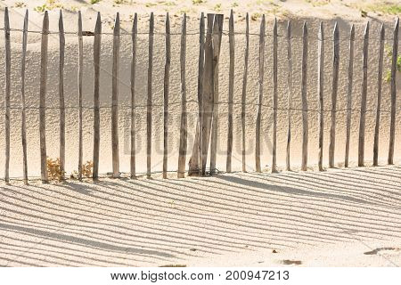 Wooden fence on an Atlantic beach in France The Gironde Department. Shot with a selective focus