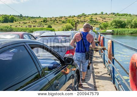 Ukraine Southern Bug River - 4 June 2017: Ferry crossing. The ferry moves with the help of a man's muscular strength. Repels from the steel cable. Such a ferry is unique in Ukraine.