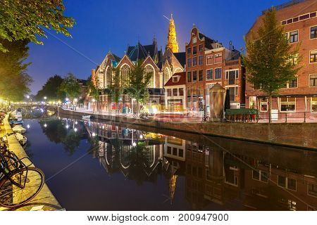 Night red-light district De Wallen, canal Oudezijds Voorburgwal and Oude Church and its mirror reflection, Amsterdam, Holland, Netherlands.