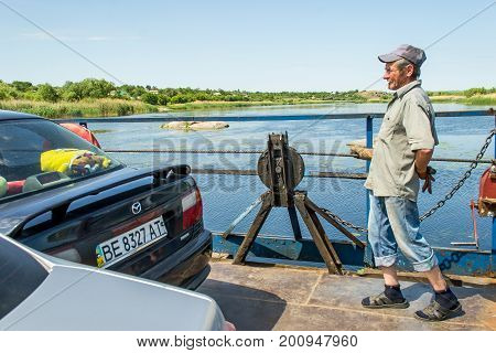 Ukraine the Southern Bug River - 4 June 2017: crossing. The ferry moves by the muscular strength of man. Repels from the steel cable. The ferryman moves this floating object.