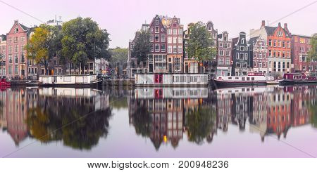 Panorama of Amsterdam canal Amstel with typical dutch houses and houseboat from the boat in the morning, Holland, Netherlands.