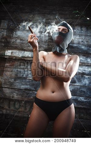 A Sexy Bandit Girl Wearing A Masked Balaclava, Naked With An Open Chest Stands Against The Wall, Wit