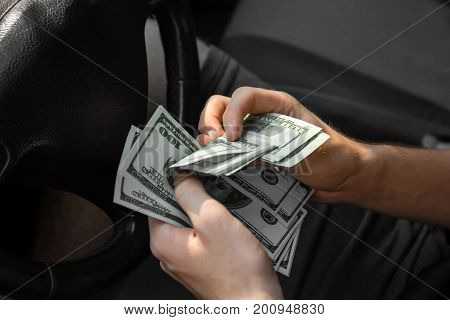 Strong man's hands counting paper money in a new automobile on a blurred black background. A successful male holding hundreds of dollars in cash. Salary, earning, payment, payout concept.