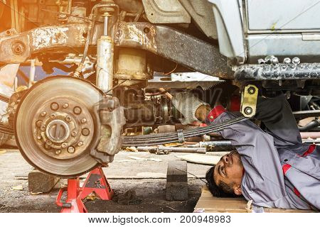 Technicians in grey uniform are repairing the axle of a car which is the car's propulsion system Automotive industry and garage concepts.