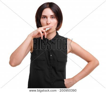 Portrait of a female nicotine addict smoking many cigarettes isolated on a white background. A beautiful brunette girl with a stylish haircut in a black blouse, holding cigarettes.