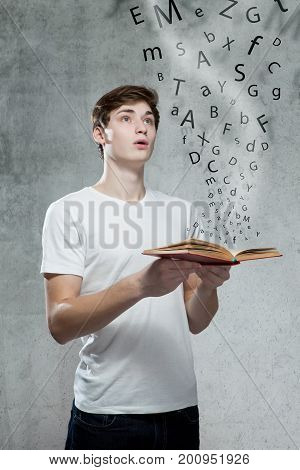 Young Man Holding A Book With Alphabet Letters