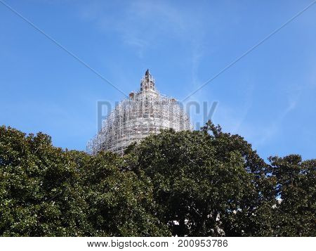 scaffolding on Capitol Hill peeks through trees on a clear blue day