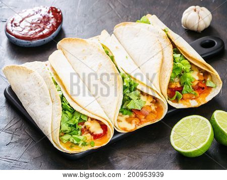 Three homemade tacos with chicken, vegetables and salsa. Latin food tacos on black wooden cutting board over black table