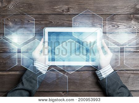 Top view of woman in business suit sitting at table and tablet device