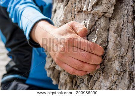 Closeup of female hand rock climbing. Bouldering in nature.