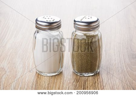 Salt And Pepper In Glass Jars On Table