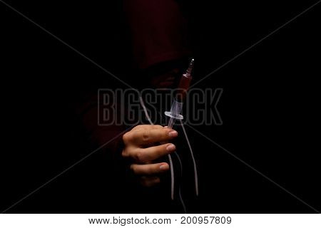 Close-up of man's hand holding a drug syringe on a black background. A creepy, suffering drug addict in a dark red hoodie. Youth in need of treatment of drug cravings and addiction concept.