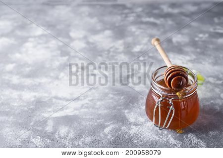 Honey. Dripped honey. Sweet honey in a jar on a stone background