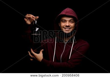 A smiling student showing a full bottle of beer or liquor standing on a black background. A handsome, boozed young male wearing a loose red hoodie, holding a bottle of light alcohol.