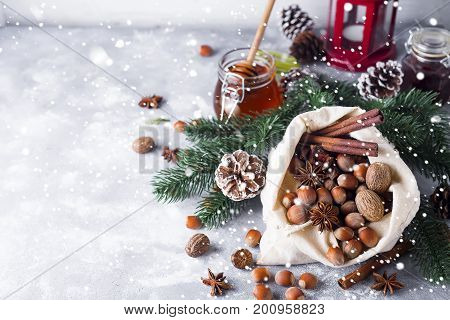Festive christmas nuts and spices tumbling from a burlap bag onto fresh winter snow with sunlight catching twinkling falling snowflakes and copysapce