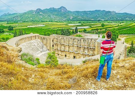 The young female tourist watches the ancient Aspendos amphitheater and the landscapes of Serik from the top of the hill Turkey.