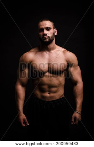 Close-up of a fashion portrait of a muscular sexy man on a saturated black background. An athletic man showing muscles. Personal trainer with big biceps. Sports concept.