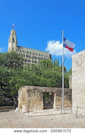 Entrance to the Alamo Mission grounds with the state flag and the historic Emily Morgan Hotel in the background in downtown San Antonio Texas