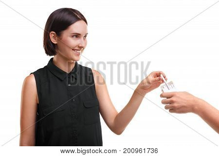 Irresponsible, carefree female student taking a cigarette from stranger's hand isolated on a white background. A girl with a stylish haircut in casual clothes taking a harmful nicotine cigarette.
