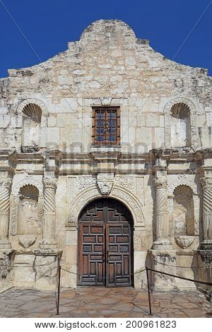 Closeup of the front entrance to the chapel of the Alamo Mission against a bright blue sky in downtown San Antonio Texas