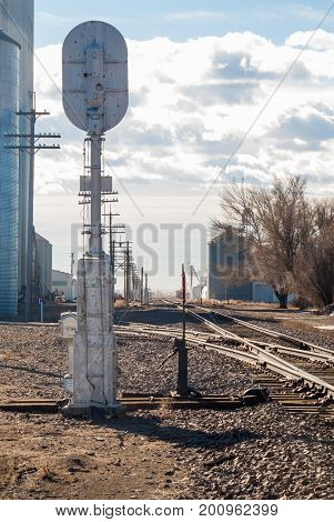 Signal stands next to a switch and tracks running through a small rural town.