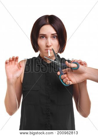 Portrait of a girl addicted to smoking and a doctor's hand cutting a cigarette with scissors isolated over the white background. Nicotine smoking is harmful and risky for your health concept.