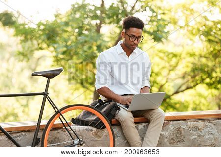 Picture of young african handsome man early morning with bicycle outdoors. Looking aside using laptop computer.