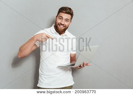 Happy bearded man holding a laptop computer and pointing at him while looking at the camera over gray background
