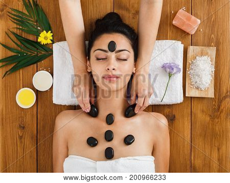 Black marble stone face massage in indian spa, top view. Female patient in wellness center. Professional massagist make relaxation procedure to beautiful girl in beauty parlor