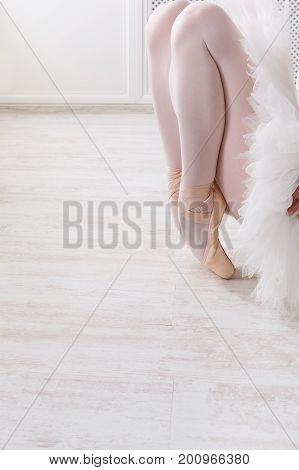 Beautiful young ballerina in pointe shoes at white wooden floor makes ballet leg stretching. Ballet practice of classical dancer, copy space
