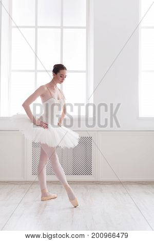 Beautiful graceful ballerina practice ballet positions in tutu skirt near large window in white light hall. Classical ballet dancer side view, copy space