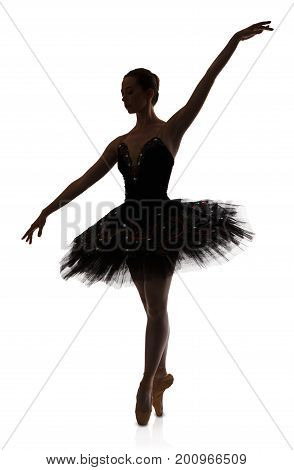 A ballerina silhouette making arabesque against white background, isolated. Professional dancer in tutu skirt. Choreography classes concept