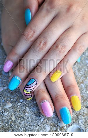 French manicure - beautiful manicured female hands with sea and summer manicure with rhinestones on background seashells