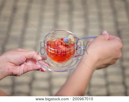 A top view of woman's hands is holding a glass full of fruity red drink on a blurred background of a road. A glass of strawberry and currant balsamico herbal tea with cubes of sugar. Healthy beverage.