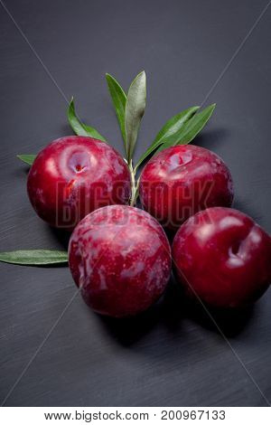 Fresh plums on black wooden table
