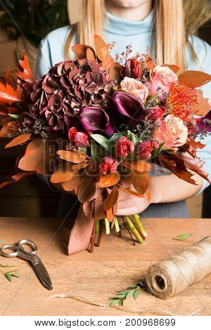 Female florist holding colorful fall bouquet at flower shop. Floristic design and delivery concept