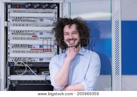 portrait of young handsome business man engeneer in datacenter server room