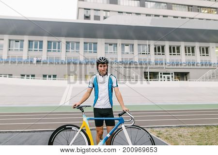Portrait of a young professional cyclist who is standing by a bicycle on the background of a velodrome.