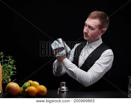 Confident, beautiful barman cleaning a shaker or a glass on the black background. Fruit ingredients for cocktails on a bar counter and a club bartender in black and white classic suit. Copy space.
