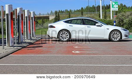 PAIMIO FINLAND - JUNE 3 2017: White Tesla Model S electric car charges battery on Tesla Supercharger Station in Paimio Finland on a sunny day.