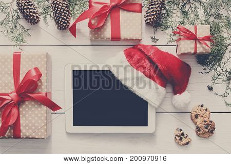 Christmas online shopping background. Tablet screen with copy space top view on white wood, present boxes, santa hat and cookies. Electronic devices, internet commerce on winter holidays concept