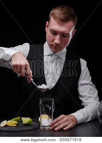 An attractive barman in a white shirt and black jacket making a shake. A club bartender adding crushed ice in a tall glass for a cold alcoholic drink on a bar counter on the black background.